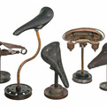 Group of 5 Vintage Bicycle Seats Mounted on Rustic Stands